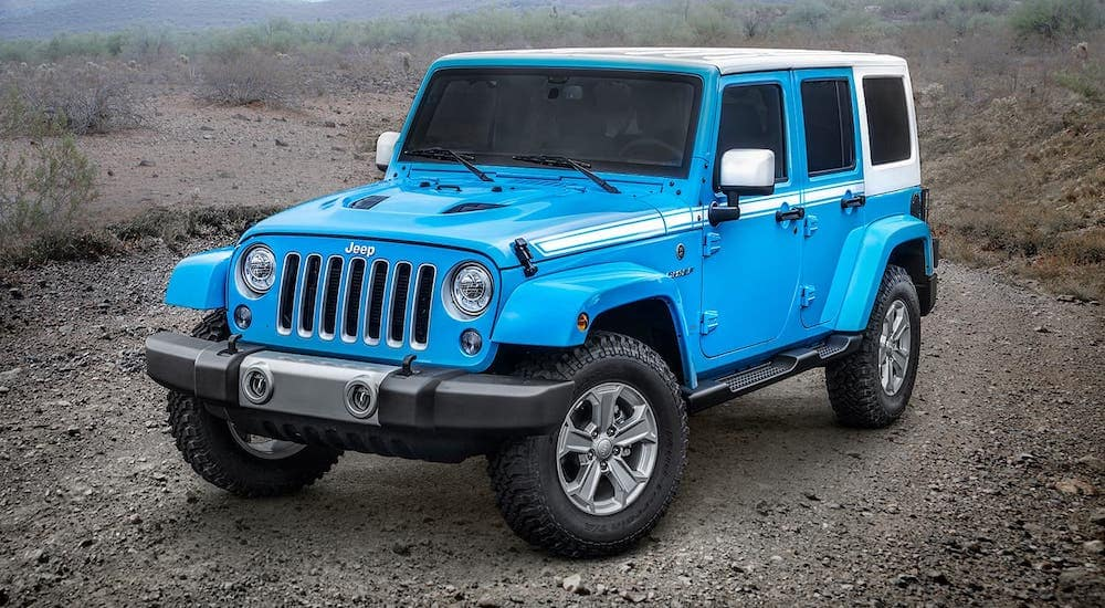 A blue 2017 used Jeep Wrangler Unlimited Chief Edition with a white hard top is parked on a dirt road outside Cincinnati, OH.