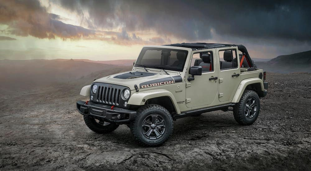 A tan 2017 used Jeep Wrangler Unlimited Rubicon with no roof is parked in a desert at sunset.