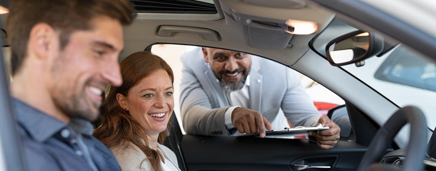 A salesman leans into a car window to show a couple features inside the car at a buy here pay here dealer near Dayton, OH.