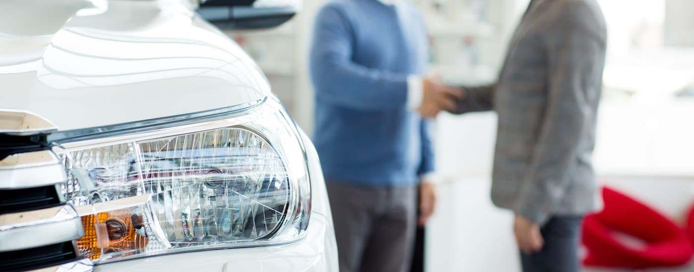 A closeup is shown of a white car's headlight while someone shakes hands with a salesman in the background.