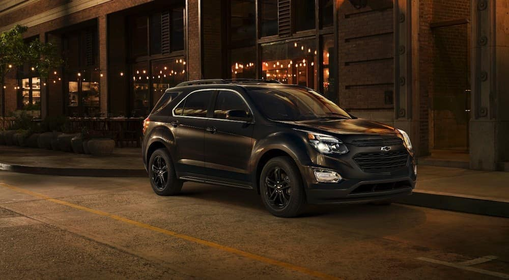 A black 2017 Chevy Equinox is parked on a city street at night in Cincinnati, OH.