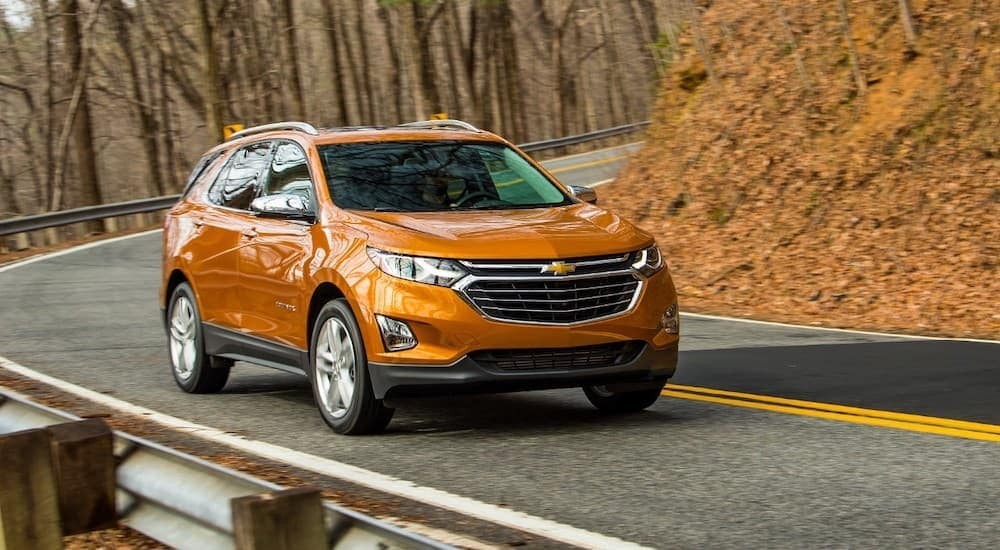 An orange 2018 Chevy Equinox is driving around a corner on a road with fall foliage.