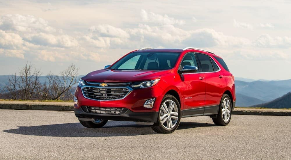 A red 2019 Chevy Equinox is parked with a view of distant hills.