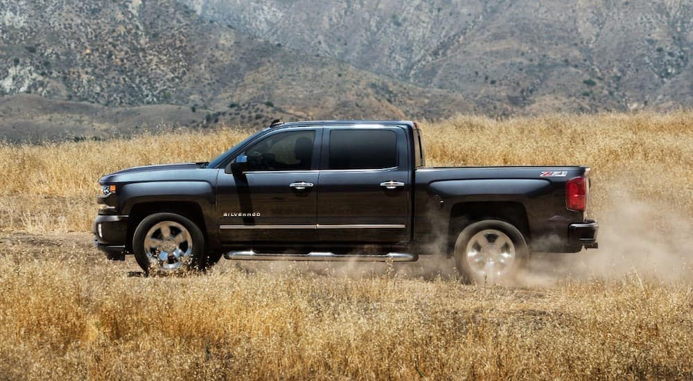 A dark grey 2018 Chevy Silverado is driving on a dirt road through a field.