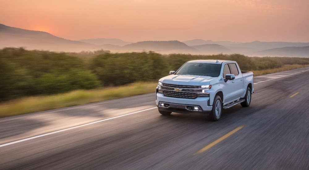 A white 2020 used Chevy Silverado is driving at sunset with mountains in the distance.