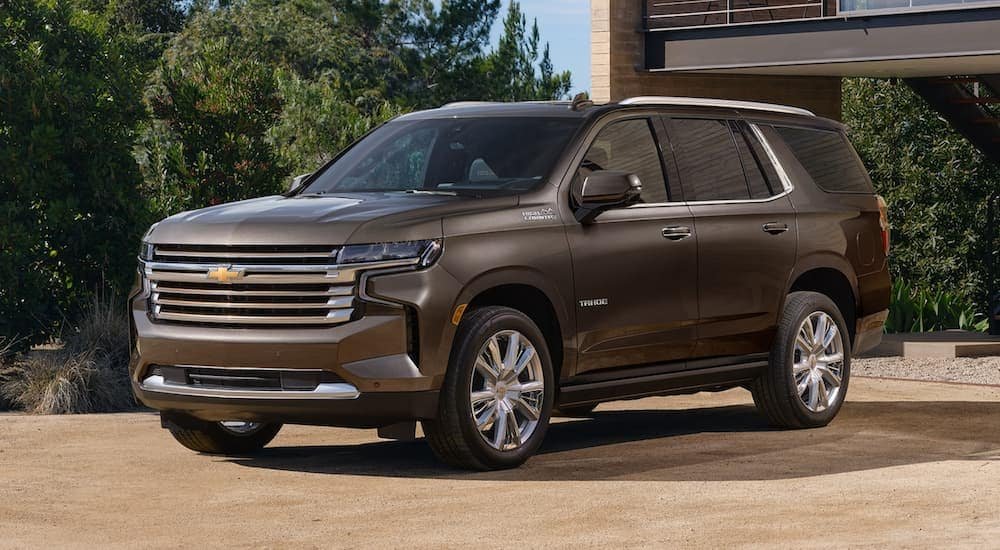 A grey 2021 Chevy Tahoe is parked in front of a modern home.