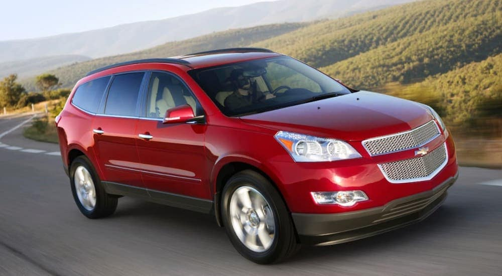 A red 2012 Used Chevy Traverse is driving on a winding road.