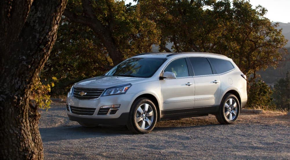 A silver 2013 Used Chevy Traverse is parked in front of trees near Cincinnati.