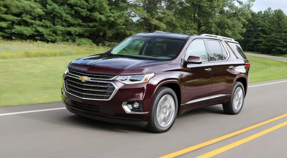 A purple 2018 Used Chevy Traverse is driving on a tree-lined road.
