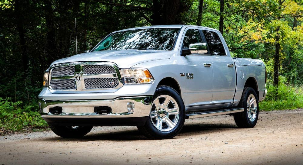 A silver 2018 used Ram 1500 is on a dirt road lined by trees.