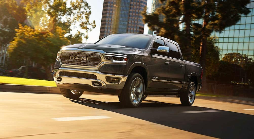 A grey 2019 used Ram 1500 is driving on a sunny city street in Cincinnati, OH.