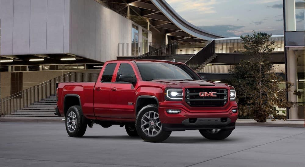 A red 2018 used GMC Sierra is parked in front of a modern building.