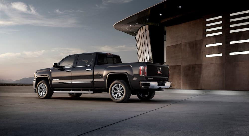 A black 2018 used GMC Sierra is shown from the rear parked at a modern building near Cincinnati, OH.