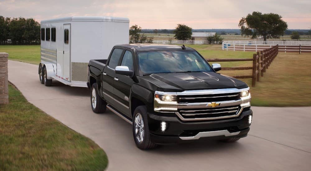 A black 2018 Chevy Silverado is towing an enclosed trailer out of a ranch.