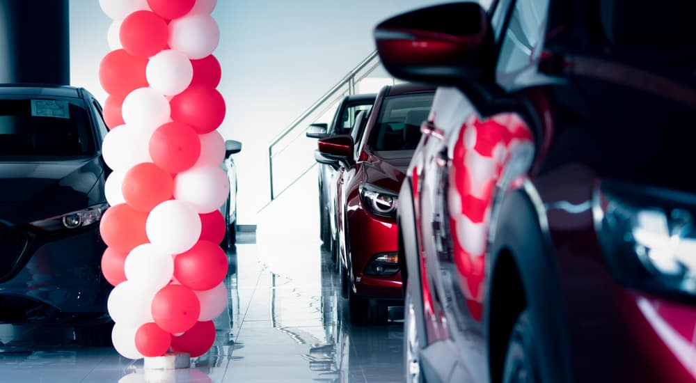 Black and red vehicles parked in a dealership showroom with a pole of white and red balloons in the middle