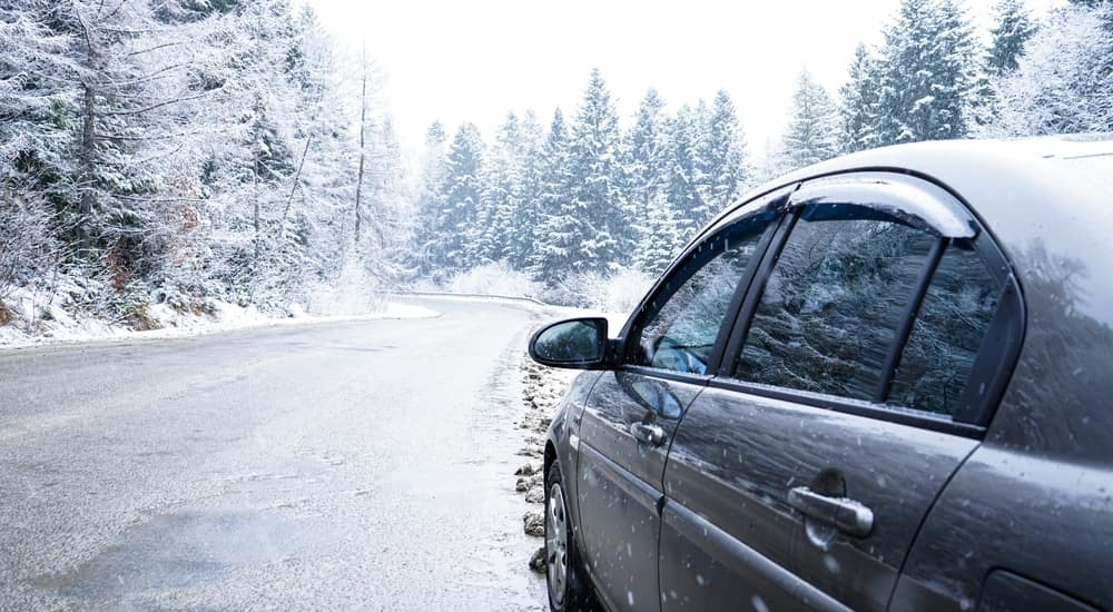 Back-to-front view of a grey sedan driving on a snowy road with snow covered trees surrounding it