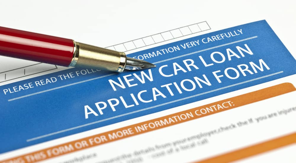 Red and silver pen sitting on top of a white, blue, and orange car loan application form