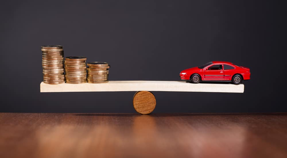 White plank sitting on a brown piece of wood with a red toy car on one side and gold coins on the other