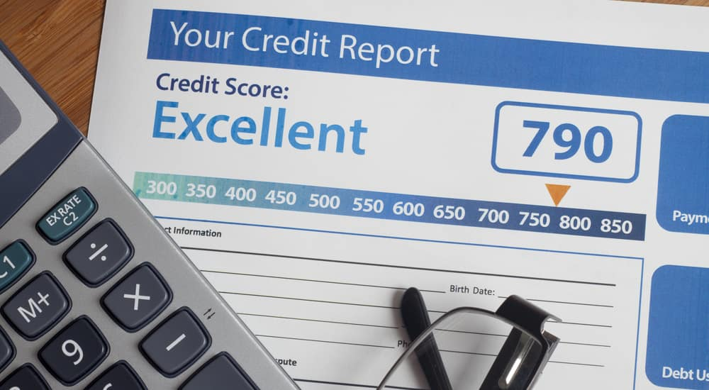 Grey calculator and black-framed glasses on top of a blue and white credit report paper