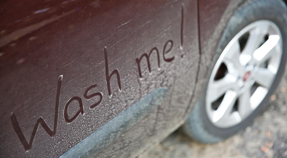 """Back door of red vehicle, covered in dirt, with """"Wash Me!"""" written in the dirt"""