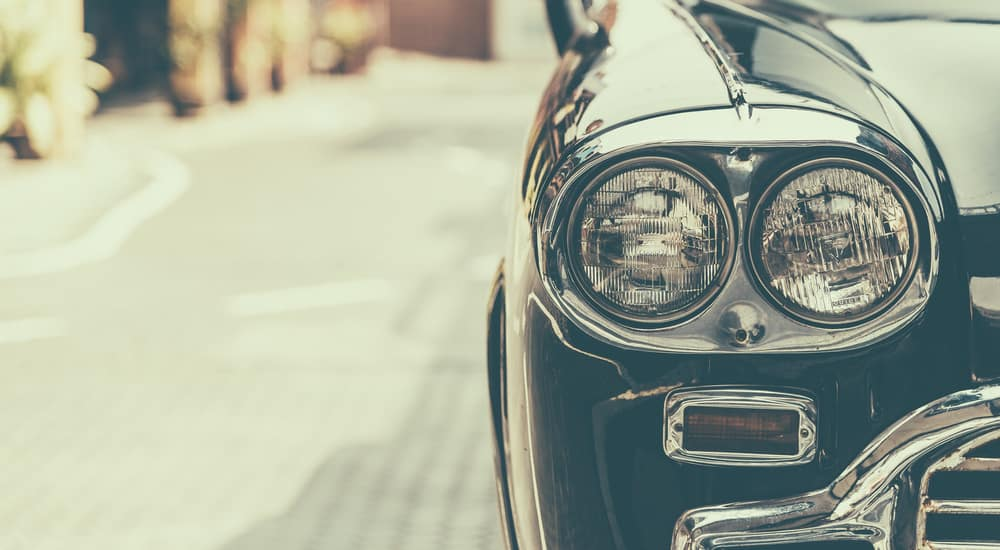 Close-up of headlight on a black vintage car on the road