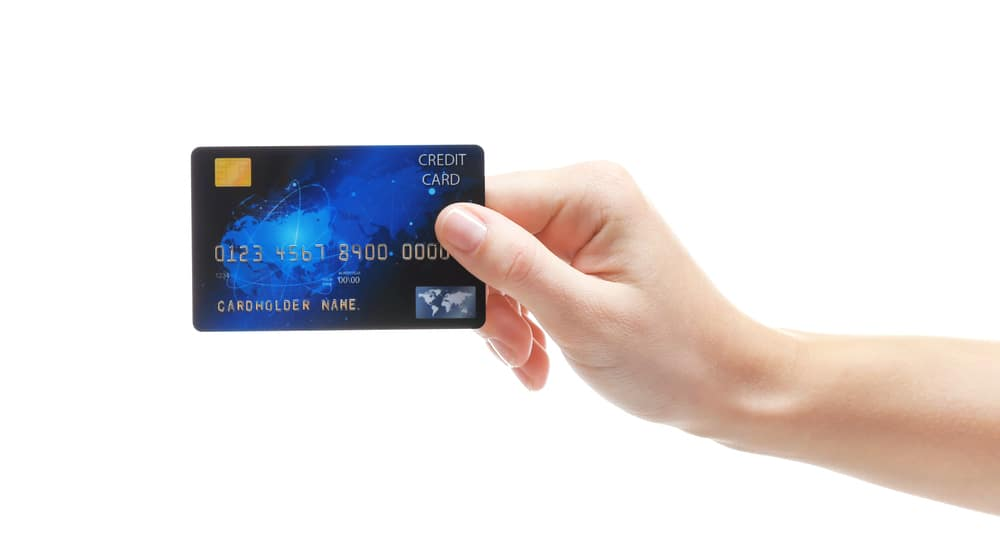 Hand holding up a blue credit card against a white background