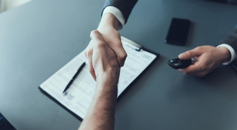Aerial view of a handshake over a cell phone, car key, and clipboard