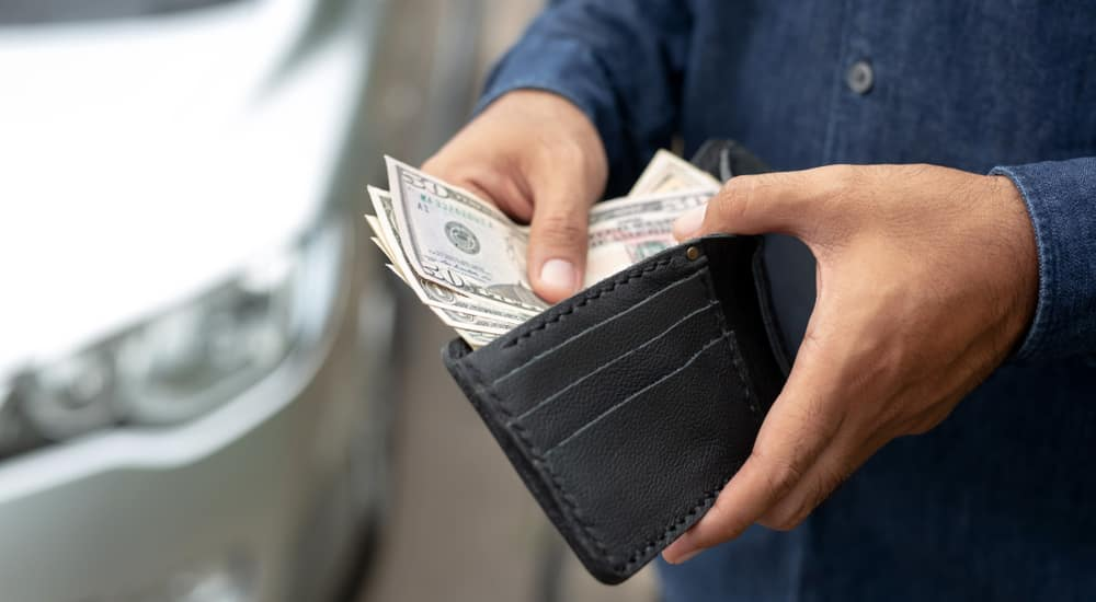 Black wallet with cash coming out being held by a man in a blue shirt in front of a silver car