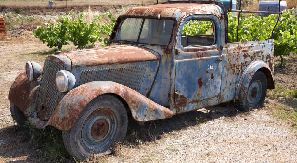 Blue, rusted truck on a dirt ground with green plants in the background