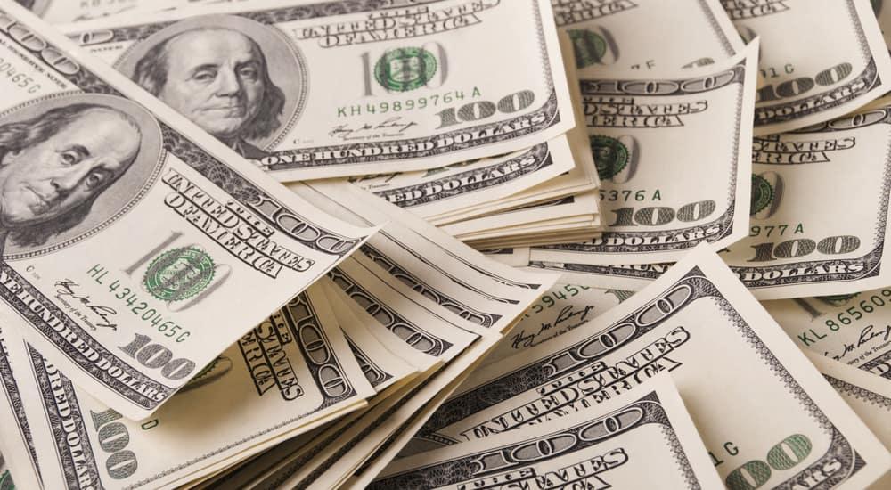 Scattered pile of one-hundred dollar bills