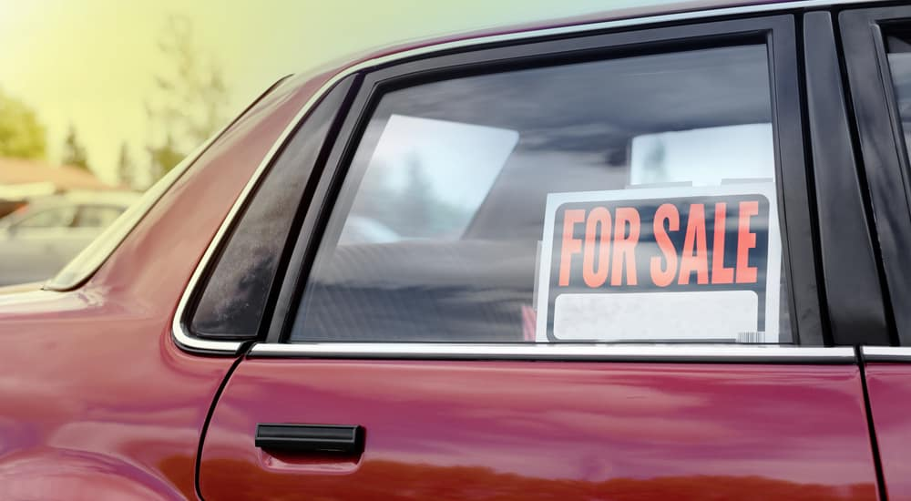 """Orange, black, and white """"FOR SALE"""" sign in the passenger window of a red car"""