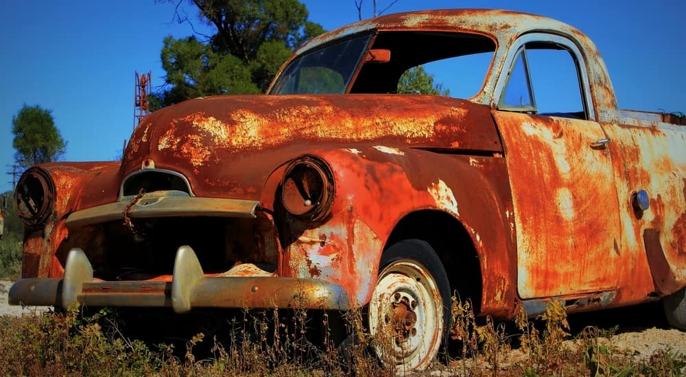 Vintage blue, rusted truck in the grass
