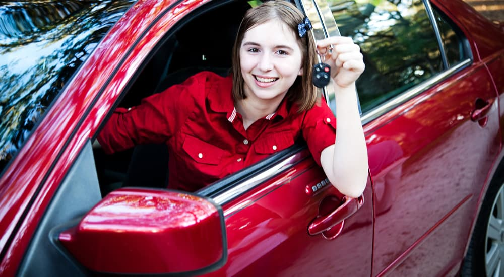 Young girl in a red shirt sitting in the driver's seat of a red sedan, holding up a car key