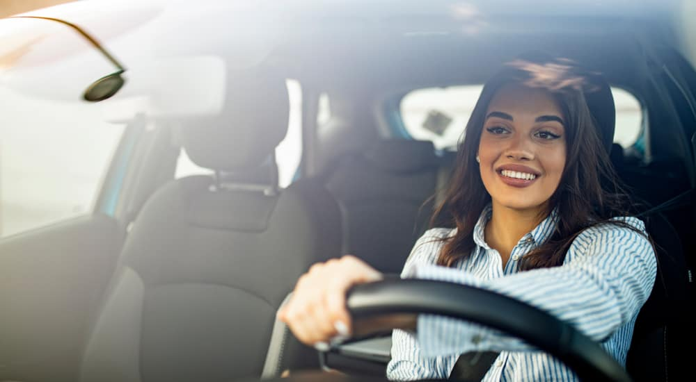 A woman in a blue and white button-up is shown driving a car.