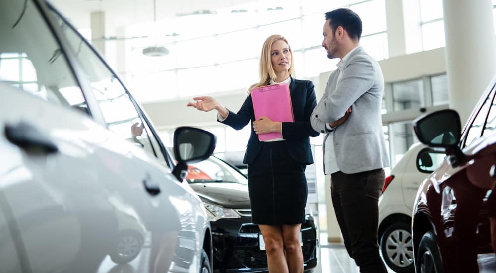 Woman in a black skirt suit with a clipboard, talking to a man in a button-up shirt surrounded by cars in a dealership showroom