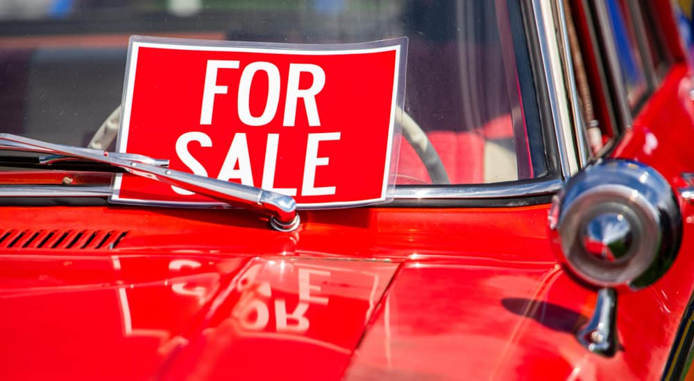"""Red retro car with a red and white """"For Sale"""" sign in the front window"""
