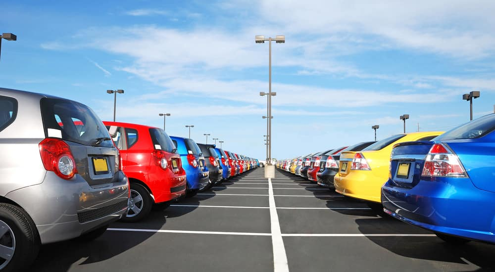 Grey, blue, red, and yellow cars parked in parking spaces with their backs facing one another