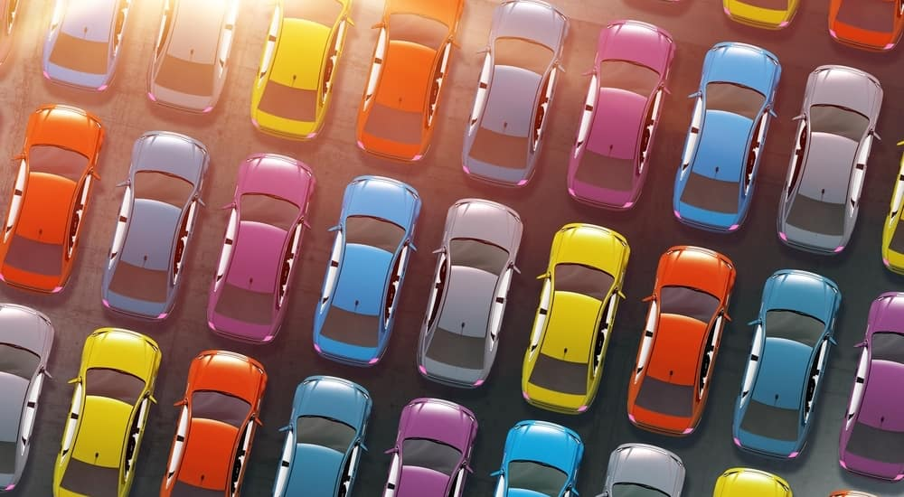 Aerial view of blue, red, yellow, purple, and grey sedans parked in a parking lot