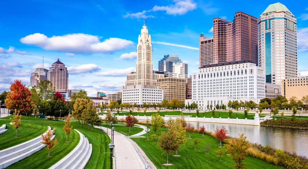 Large river, trees, grass, and sidewalks perpendicular with tall Columbus OH buildings