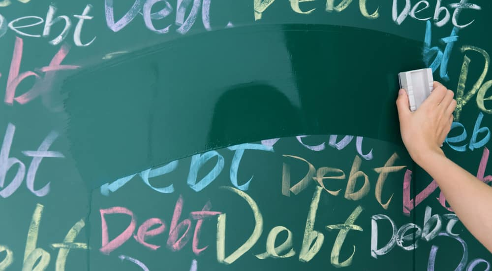 """Green chalkboard with the word """"debt"""" written in various colors on it, and someone erasing all of the words"""