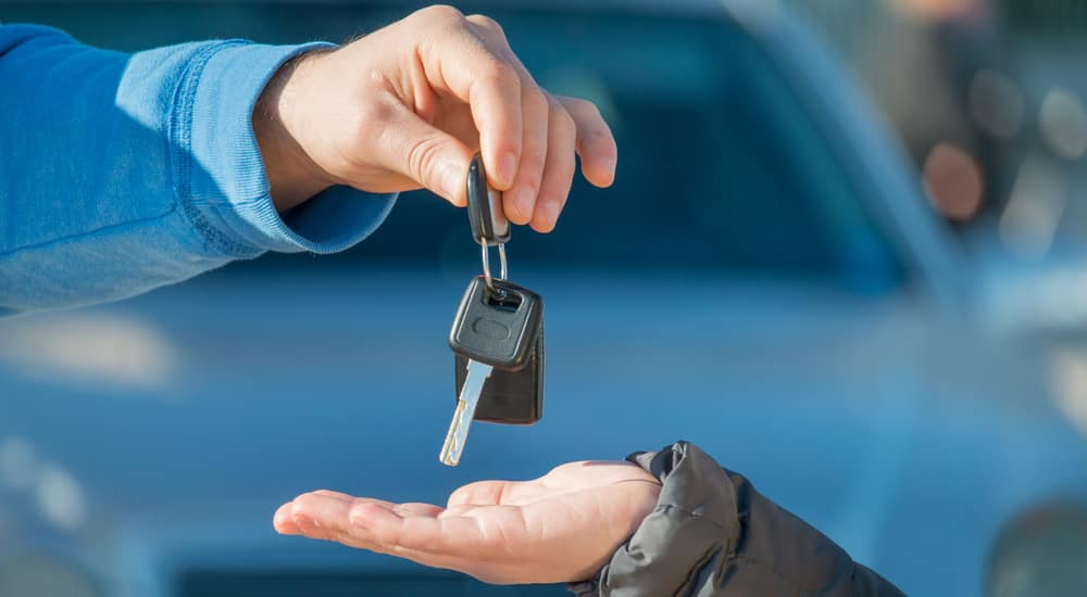 One hand placing car keys in another hand in front of a blue vehicle