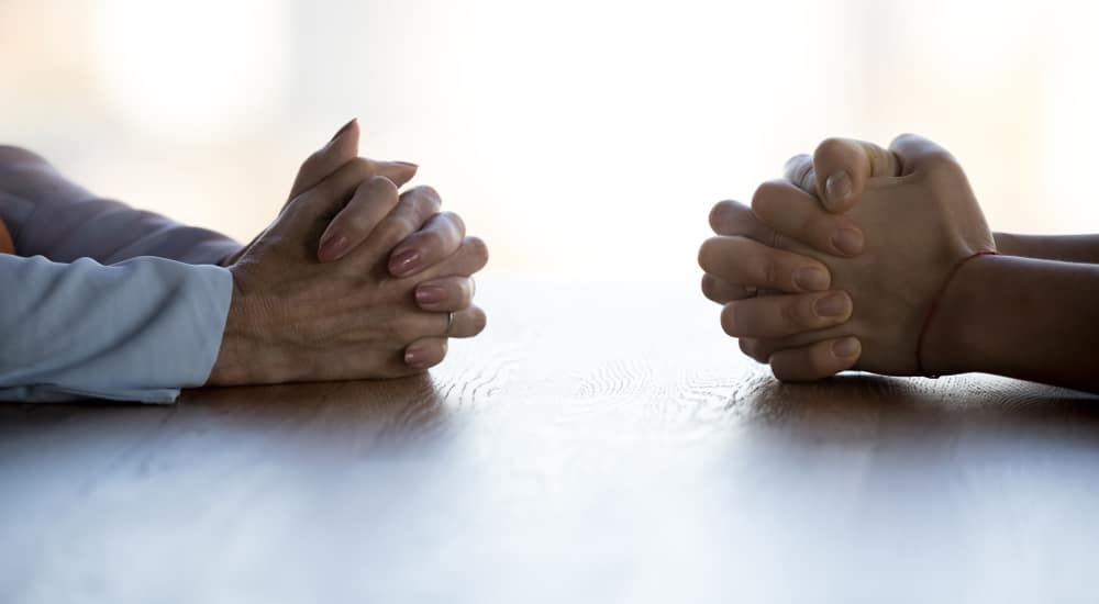 Two sets of hands folded across from one another on a table