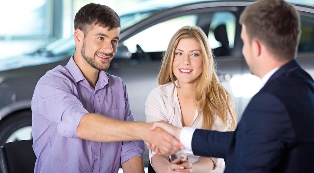 Man in a purple button-up shaking hands with a man in a suit and sitting next to a woman in a white shirt in front of a silver car