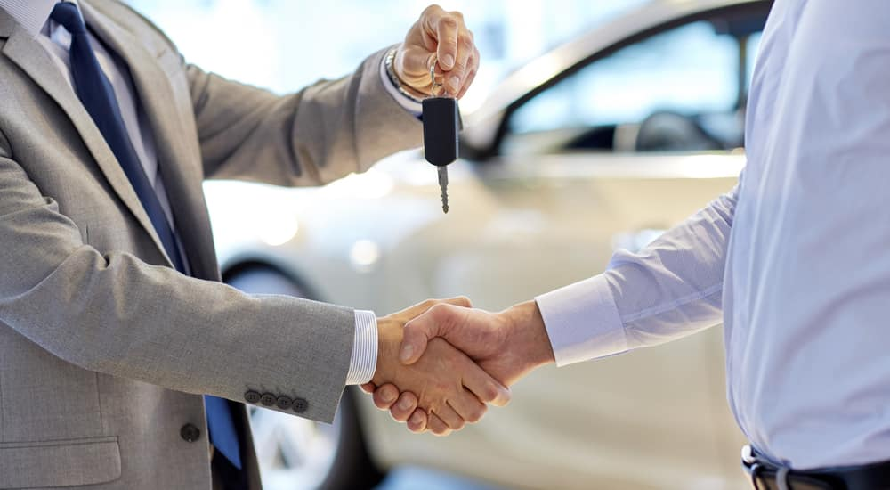 Man in a grey suit and a blue tie handing a car key to and shaking hands with a man in a blue shirt in front of a white car