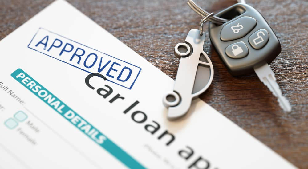 """Car key with a car keychain on it sitting on top of a blue and white car loan application with """"APPROVED"""" stamped on it"""