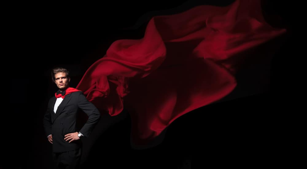Man wearing a suit with his hands on his hips and a red cape flowing behind him