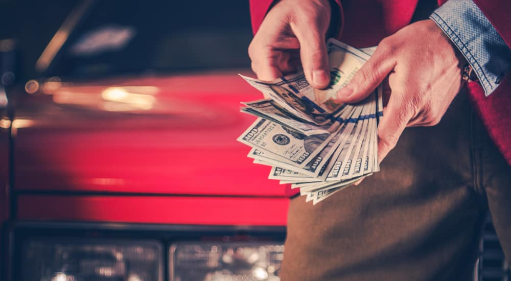 Hands holding one-hundred dollar bills in front of a red vehicle