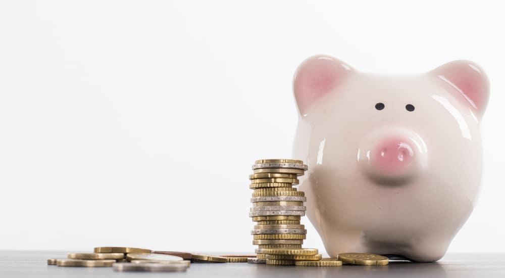 Pink piggybank next to piles of coins