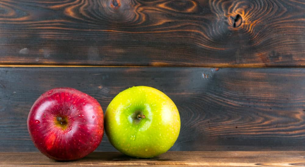 Top view of one red and one green apple sitting on a dark wood table