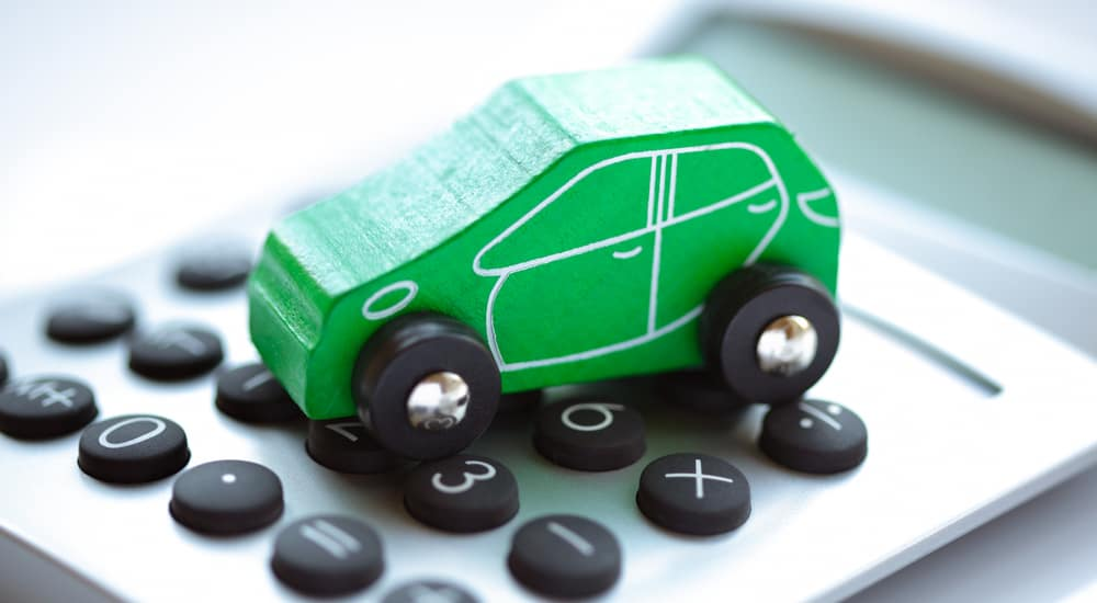 Green, wooden toy car with black tires sitting on top of a grey and black calculator